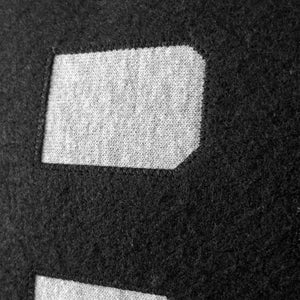 A closeup of the embroidered black felt B on the chest of an Oxford heather gray sweatshirt, showing the quality and texture of the embroidery.