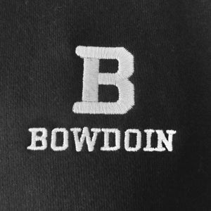 Closeup of black sweatshirt showing the high quality embroidery of the Bowdoin B embroidered over the word BOWDOIN in white.