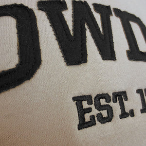 Closeup shot showing raw edges of jersey-knit black applique letters and black embroidery.