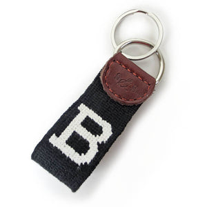 Needlepointed keyfob decorated with a white Bowdoin B on a black background. Small leather tab at the end attaching the metal key ring, debossed with the S&B logo.