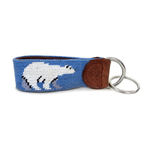 Needlepointed keyfob decorated with a white polar bear on a light blue background. Small leather tab at the end attaching the metal key ring, debossed with the S&B logo.