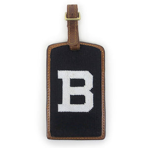 Brown leather luggage tag with brass buckle and needlepointed Bowdoin B backing.