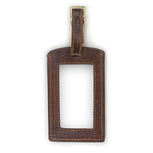 Reverse view of brown luggage tag showing window for contact information.