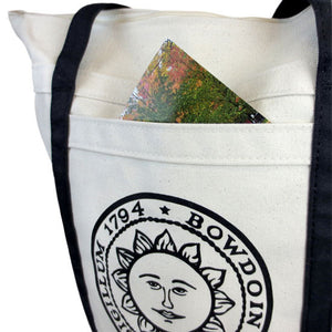 Closeup showing a postcard poking out of the pocket of a Bowdoin seal tote bag.