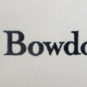 Closeup of the letters BOWD embroidered in black on natural canvas.