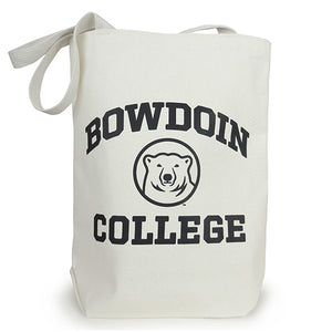 A natural-colored canvas tote bag with black BOWDOIN COLLEGE and polar bear medallion imprint. BOWDOIN is arched over the bear head medallion, and COLLEGE is in a straight line underneath the medallion.