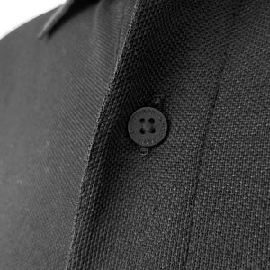 Closeup of button on black polo showing CUTTER & BUCK imprint on button.