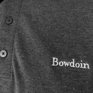 Closeup of embroidery and buttons on grey polo shirt.