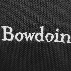 Closeup showing white embroidery on black polo shirt.