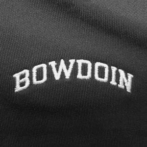 Closeup of white arched BOWDOIN embroidery on black polo shirt.
