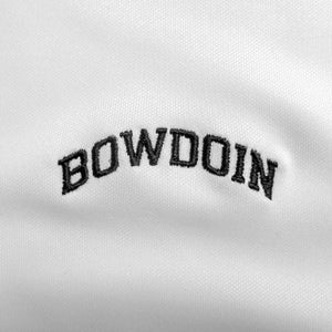 Closeup of black arched BOWDOIN embroidery on white polo shirt.