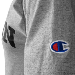 Closeup shot of the left sleeve of a short-sleeved Oxford heather gray T-shirt showing an embroidered Champion C logo patch in red, white, and blue.