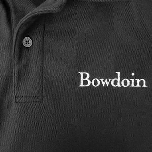 Closeup showing L.L.Bean branded button and white Bowdoin embroidery on polo shirt.