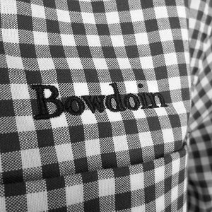 Closeup shot of the word BOWDOIN embroidered over the pocket of a black and white gingham check dress shirt.