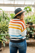 "Load image into Gallery viewer, This sweater features a round neckline, long sleeves, a striped print featuring orange, yellow light blue, teal and black ascending stripes  Fabric:  Approx Measurements:  Small: Bust 44"", Length 23""  Medium: Bust 46"", Length 23""  Large: Bust 48"", Length 24""  XLarge: Bust 50"", Length 25""  Model Corin: 5'5 size 11/12 wearing Large"