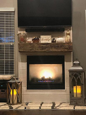 Reclaimed wood beam mantle over fireplace