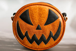 Small glitter orange scary smiling jack o lantern purse with orange stitching and black eyes and mouth
