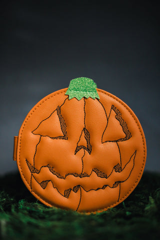Orange jack o lantern wallet on grass with a night sky behind it.