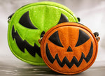 Small glitter orange scary smiling jack o lantern purse with orange stitching and black eyes and mouth In front of a green glitter larger jack o lantern purse with black eyes and mouth and green stitching