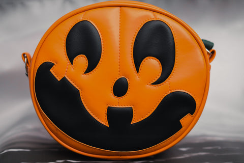 Orange and Black silly face pumpkin handbag on grey background.