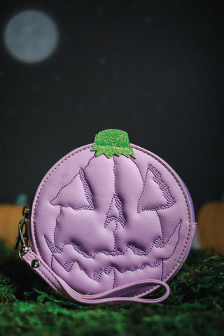 Circle jack o lantern in lilac, photographed on grass with a night sky, moon, and pumpkins behind.