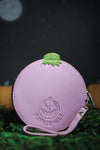 Back of circle jack o lantern wallet in lilac photographed on grass with night sky, moon, and pumpkins in the background.