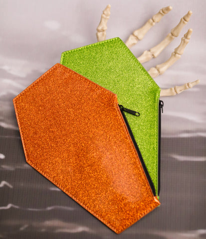 Orange glitter coffin shaped coin bag with a black zipper on top of a green glitter coffin coin bag with a black zipper laying on a skeleton hand