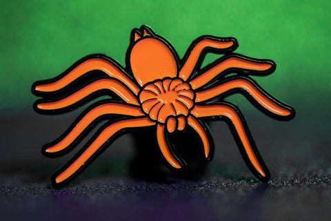 Orange spider enamel pin on green background.