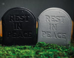"Headstone wallets with ""rest in peace"" embossed on the front on grass."