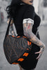 Woman wearing a black heart crossbody bag with orange spiderweb stitching and orange and black striped sides Facing backwards