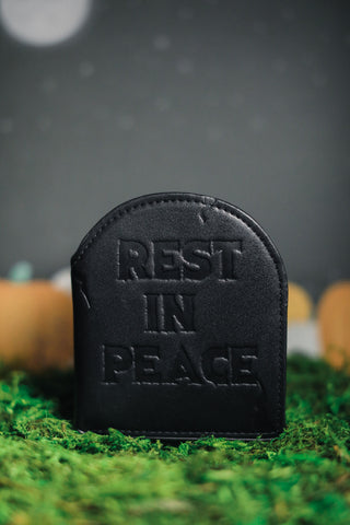 "Black ""rest in peace"" headstone wallet photographed on grass."