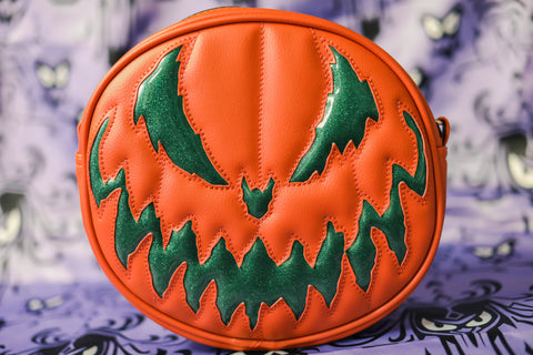 Orange pumpkin bag with sparkly dark green scary face on purple designed background.