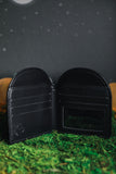 Inside of black headstone wallet on grass and night sky.