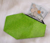 Green glitter coffin shaped coin bag with green stitching and a black zipper with two Hundred dollar bills, three quarters a nickel and a penny sticking out of it