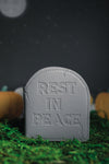 "Grey headstone wallet with ""rest in peace"" embossed on the front on grass and night sky."