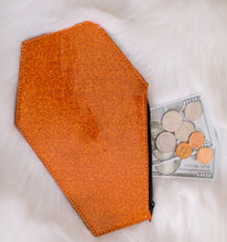 Load image into Gallery viewer, Orange glitter coffin shaped coin bag with orange stitching and a black zipper with two Hundred dollar bills, three quarters a nickel and a penny sticking out of it