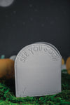 "Back of grey headstone with ""see you soon"" embossed on it."