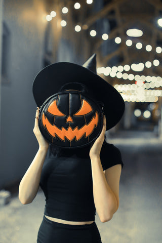 Girl holding all black pumpkin handbag with orange face and orange stitching in front of her face.