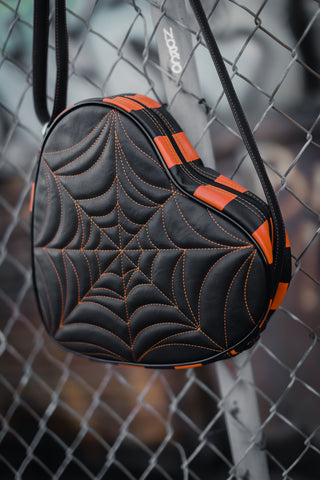 Black heart cross body bag with orange stitched spider webbing and orange and black stripes along the side hanging from a chain link fence by a long black strap with orange stitching