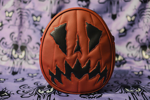 Oval pumpkin bag Scaredy Cat Wine colored vinyl with Black and matching stitching . Purple background.
