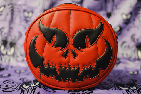 Evil pumpkin bag reddish orange and black vinyl with matching stitching. On purple designed background.