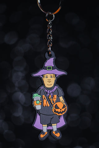 "Basic Witch kid keychain with ""pumpkin cult"" shirt, purple witch hat, purple cape, orange shoes,  pumpkin spice drink, and our signature pumpkin bag in orange and black."