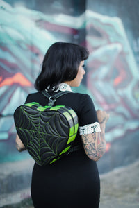 Woman wearing a black heart shaped back pack with green spider web stitches and green and black striped sides facing backwards with her head turned. The back pack strap is black and has green stitching
