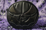 Black pumpkin with black glittery bat mouth on purple designed background.