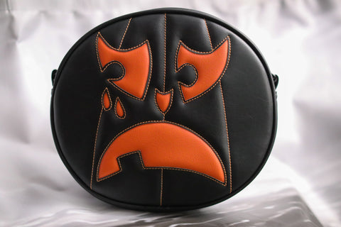 Black and orange crying pumpkin bag on white background.