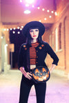 Girl wearing the black and orange pumpkin handbag with sparkly happy face. Photographed in a halfway with hanging decorative lights.