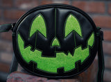 All black pumpkin bag with happy face in sparkly lime green with green stitching.
