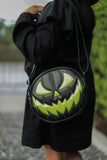 Girl holding all black pumpkin bag with scary face in sparkly lime green with green stitching.