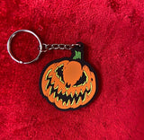 Bad company keychain of orange pumpkin with scary pumpkin face in black and yellow.