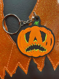 Crying pumpkin keychain in orange and black  on top of the bag in the same design.